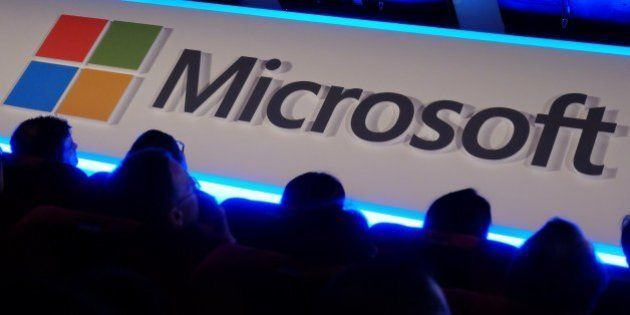International buyers listen to a speeck in front of a Microsoft logo during the Computex tech show in...