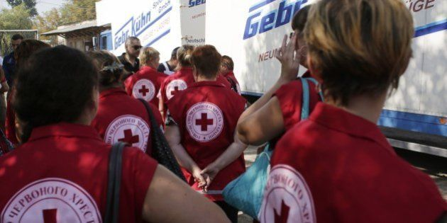Employees of the Ukrainian Red Cross organization wait before checking on food and assistance products...