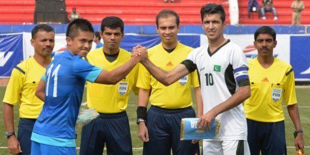 Pakistani captain Kaleem Ullah (2R) and his Indian counterpart Sunil Chhetri (2L) shake hands before...