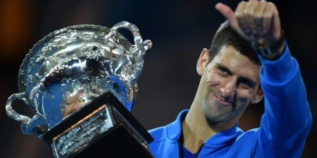 Serbia's Novak Djokovic poses with The Norman Brookes Trophy after victory in men's singles final match...