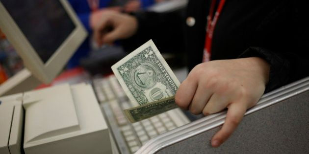 A cashier holds a U.S. one dollar bill at the checkout inside a Kmart discount store, operated Sears...