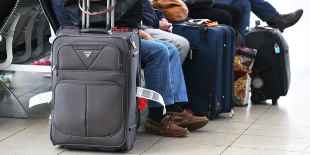 Passengers sit with their luggage while waiting to board a flight operated by Virgin Australia Holdings...