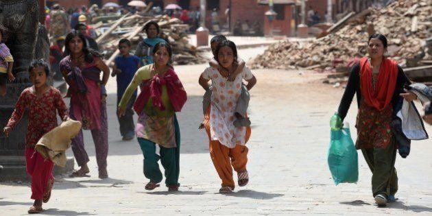 Nepalese residents carry belongings following fresh tremors in Kathmandu on April 26, 2015. International...