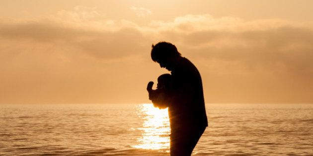 A young father walks in the early morning light carrying his baby.Father and Child. I have posted a story...