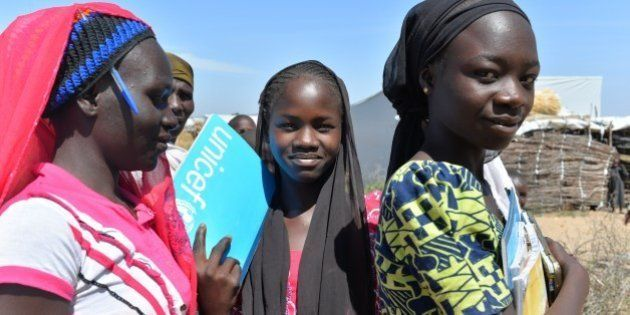 Girls carry thier school books on November 13, 2014 in a UNHCR camp for Nigerian refugees in Minawao,...