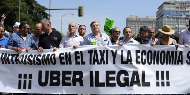 Taxi drivers carry a banner during a strike action in protest of unliscensed taxi-type-services in central...