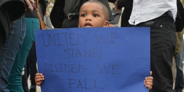A child holds a sign as demonstrators protest outside the Edward Jones Dome in downtown St. Louis, Missouri...