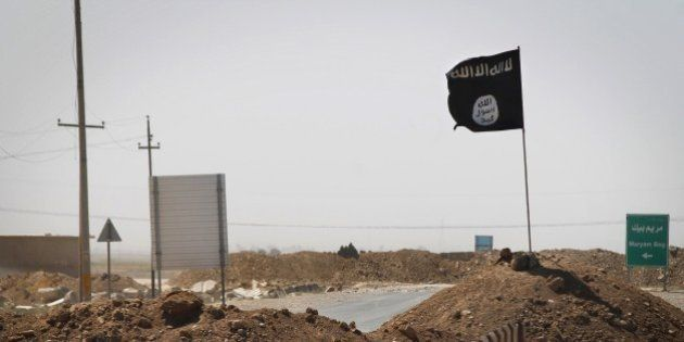 A flag of the Islamic State (IS) is seen on the other side of a bridge at the frontline of fighting between...