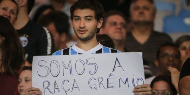 A fan of Gremio holds a message against racism during their Brazilian championship match against Flamengo,...