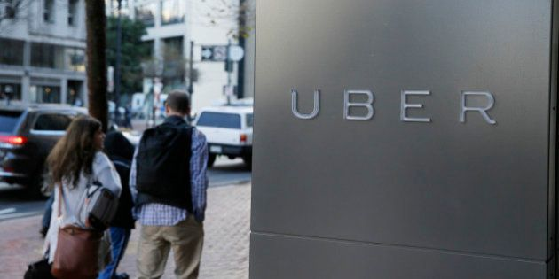 In this photo taken Tuesday, Dec. 16, 2014, a couple walks past the headquarters of Uber in San Francisco....