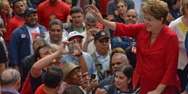 Brazilian President and presidential candidate for the Workers' Party (PT) Dilma Rousseff (R) waves to...