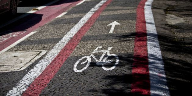 Vehicles pass by a lane dedicated to bicycles in Sao Paulo, Brazil, on Wednesday, Sept. 10, 2014. Bike...