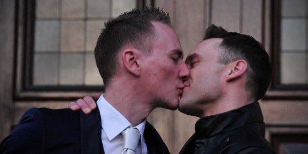 Tim Jarmaine-Groves (L) kisses his husband Richard Jarmaine-Groves after their same-sex wedding in north...