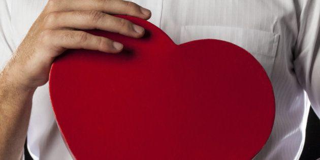 a man holding a heart gift box...