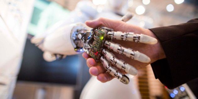 A visitor holds a hand of AILA, or Artificial Intelligence Lightweight Android, during a demonstration...