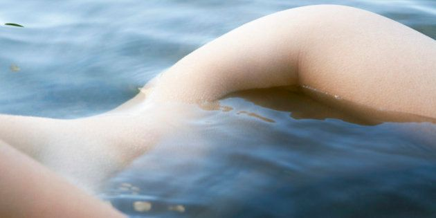 Nude young woman laying on her side in a pond almost submerged by water, front view and