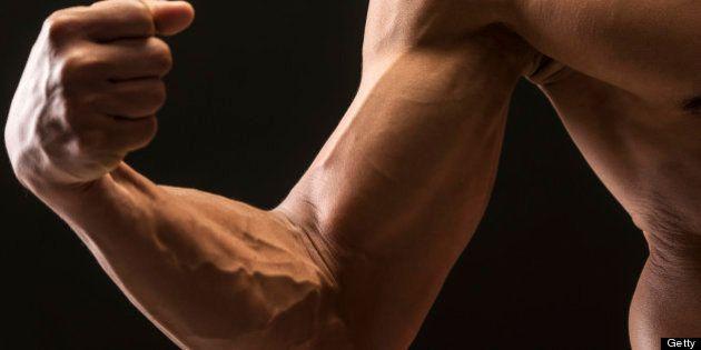 Hispanic shirtless male model showing his muscular built on black