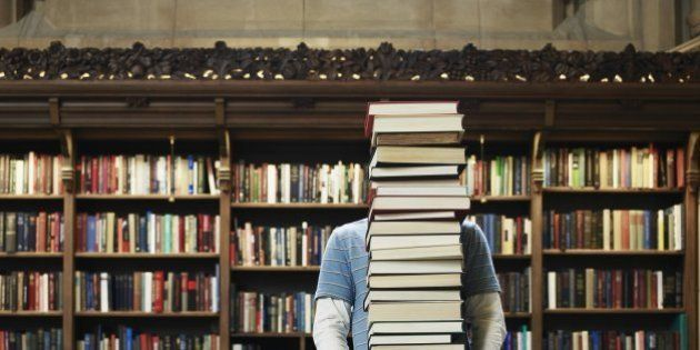 Young man carrying stack of books in university
