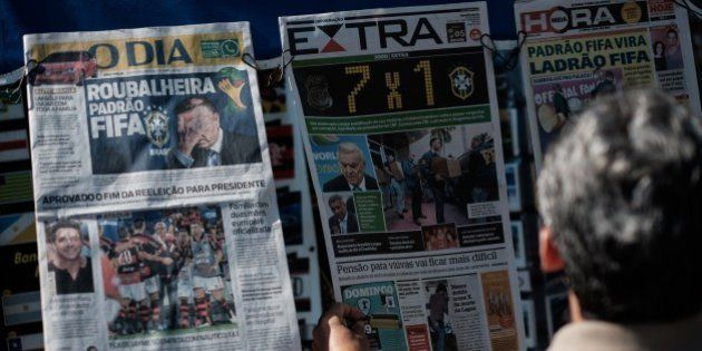 A man reads front pages of newspapers at a kiosk showing FIFA officials arrests including former president...