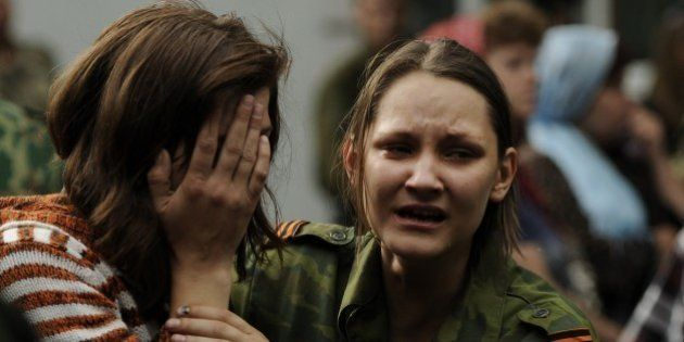 Women react near the coffin of Alexey Mozgovoy, leader of the so-called Prizrak (Ghost) brigade, during...