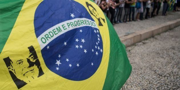 People demonstrate with a Brazilian national flag depicting the portraits of Brazilian former President...