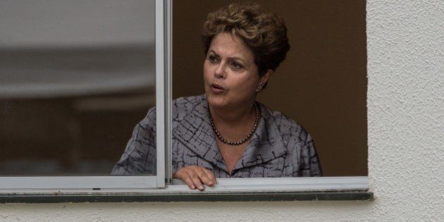 Brazilian President Dilma Rousseff looks out fron an apartment during the inauguration of the apartments...