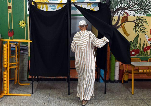 Un homme rentre dans un isoloir pour voter, lors des élections régionales et communales...