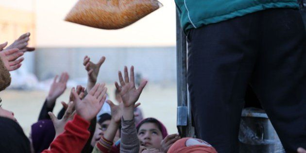 ALEPPO, SYRIA - FEBRUARY 10: Syrians, who fled bombing in Aleppo, try to get food at a tent city close...