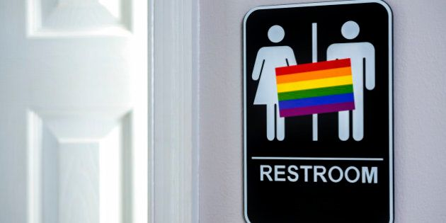 LGBT flag on a restroom sign next to a bathroom door that is ajar. There is a lot of controversy over...