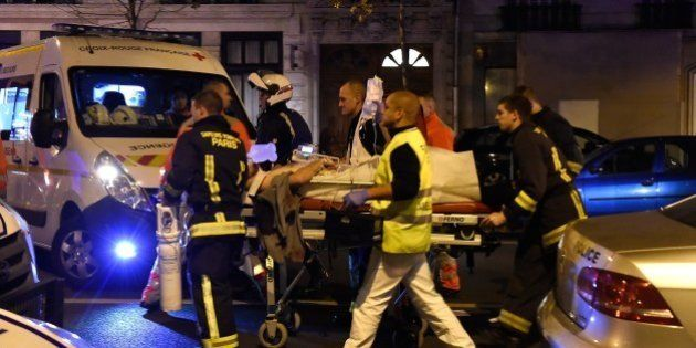 Rescuers evacuate an injured person on Boulevard des Filles du Calvaire, close to the Bataclan concert...