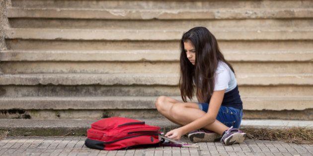 Teenage girl putting notebooks into school