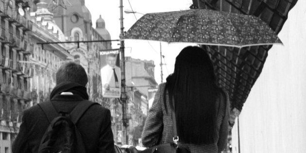 A young couple walking in Bucharest, Romania one rainy autumn