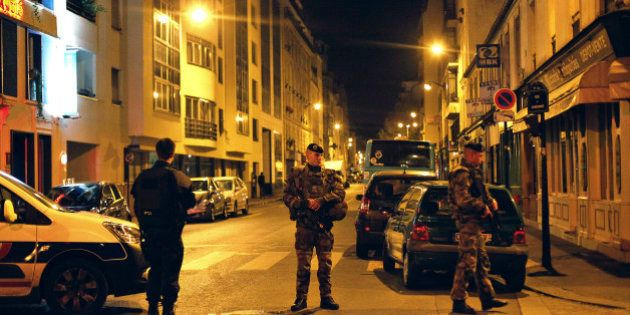French soldiers and a police officer stand on a street next to Rue de Charonne, in Paris, Saturday, Nov....
