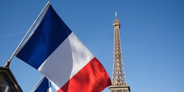 A French national flag flies near the Eiffel Tower in Paris, France on Sunday, Nov. 15, 2015. French...