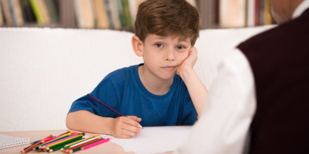 Sad little boy trying to draw in psychologist office. Focus on boy. There are many books in psychologist office