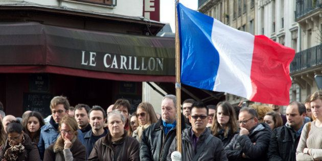 PARIS, FRANCE - NOVEMBER 16: People gather to observe a minute silence outside the Le Carillon restaurant...