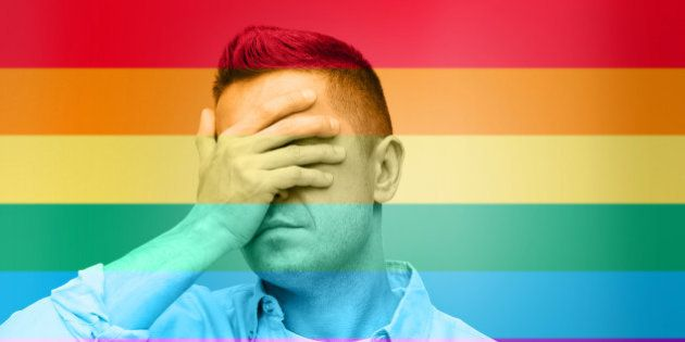homosexual, homophobia, intolerance and people concept - unhappy gay man covering his eyes by hand over...