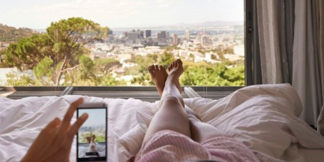 Cropped shot of a woman in bed taking a picture of the view from her