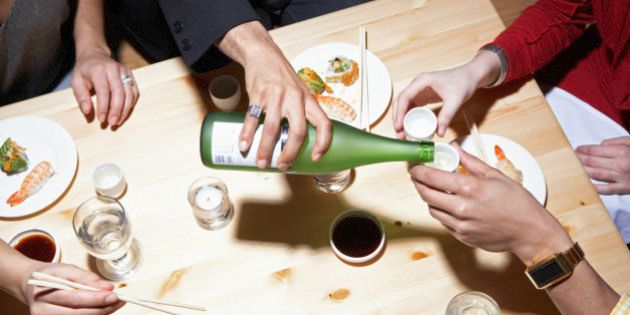 Four adults eating sushi and drinking sake, mid section, elevated