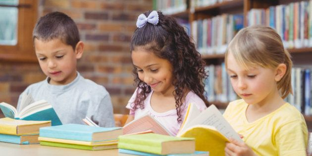 Pupils reading books in library at the elementary