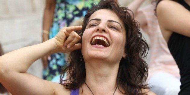 Turkish women laugh during a yoga session in a public garden in protest against Turkey's Deputy Prime...