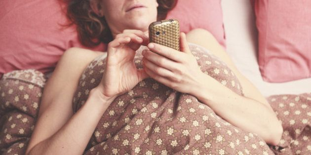 Young woman is lying in bed and sending a text on her