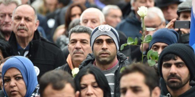 People gather during a public tribute to the victims of the November 13 series of deadly attacks in Paris...