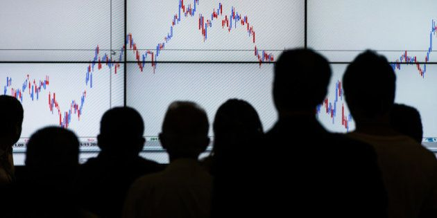 People listen to an explanation of the stock chart during the Expo Money in Sao Paulo, Brazil, on September...