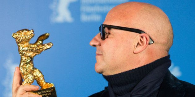 Gianfranco Rosi, director of 'Fuocomare', looks at the Golden Bear for the Best Film during the award...