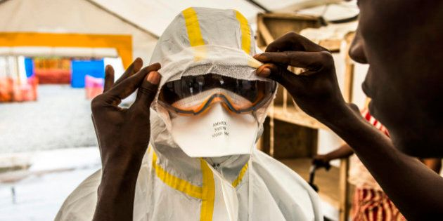 A healthcare worker assists a colleague to dress in Personal Protective Equipment (PPE) at an Ebola Treatment...