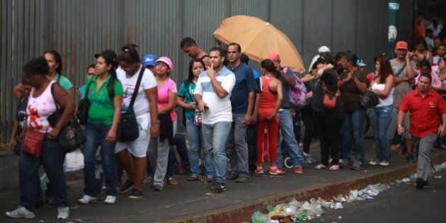 People queue up outside a supermarket to buy food in Caracas April 2, 2014. The Venezuelan government...