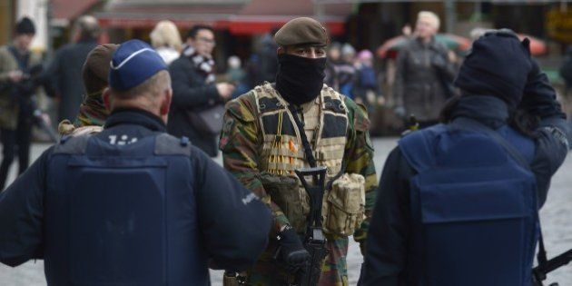 Police officers and a soldier stand on the Grand Place in Brussels on November 22, 2015. The Belgian...