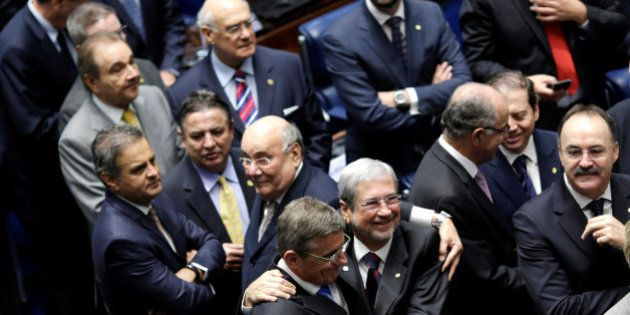 Members of Brazil's Senate react after a vote to impeach President Dilma Rousseff for breaking budget...