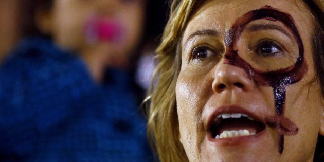 A woman attends a protest against rape and violence against women in Rio de Janeiro, Brazil, May 27,...